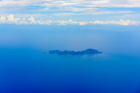 arial: Arial view from jetplane blue sky and big white cloud with green island background