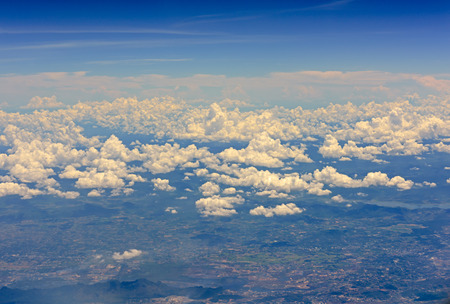 arial: Arial view from jetplane blue sky and big white cloud with green island background,out of focus