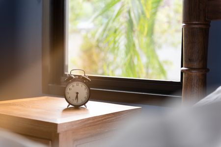 side table: Modern blue bedroom  and alarm clock on wooden side table with morning sunlight Stock Photo