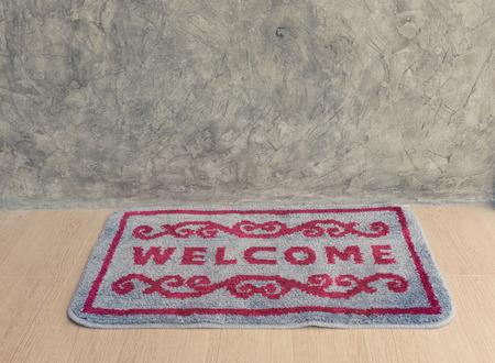 grune: Welcome door mat with grune mortat wall background,retro effect