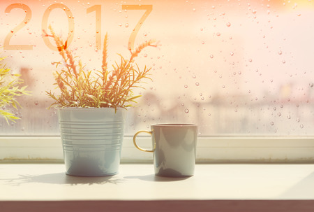 day light: Coffee cup on table with rain drop and 2017 text on window background