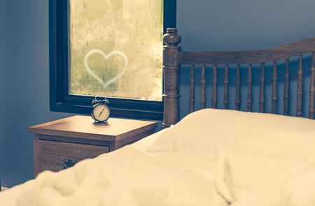 antique table: Antique alarm clock on wood table in white bedroom,retro filter Stock Photo