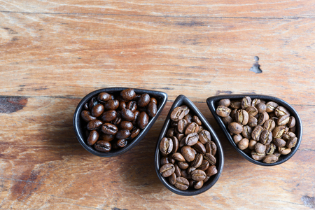 Roasted coffee beans of three different level in black bow on grunge wooden background Stock Photo