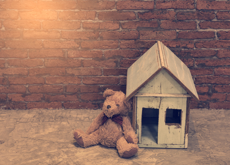 Lonely bear sitting near wooden house with brick wall background,retro effect