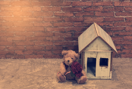 Lonely bear hold rose flower sitting near wooden house with brick wall background,retro effect