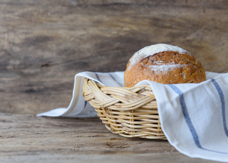 Whole wheat bread set in bamboo basket on wooden table top background Stock Photo