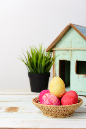 red straw: Easter eggs in basket on wooden table top with vintage house background