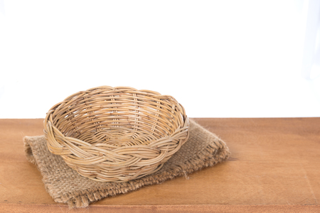 SACKCLOTH AND BAMBOO BASKET ON  WOODEN BACKGROUND WITH CLIPPING PATH Reklamní fotografie