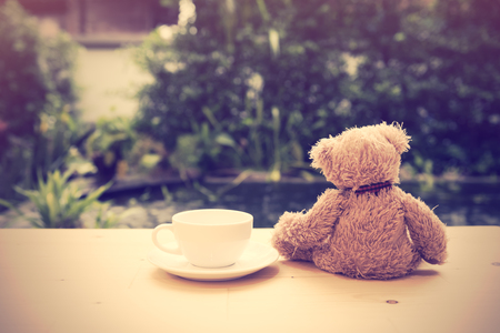 bear lake: Alone teddy bear sit back  with coffee cup on wooden floor with pool background,retro filter effect