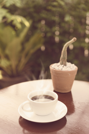 Coffee cup in morning sun light  with green garden background,retro effect Stock Photo