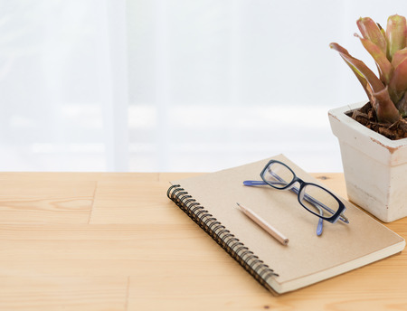 Notebook ,eyeglasses,flowerpot and brown pencil on wood table background