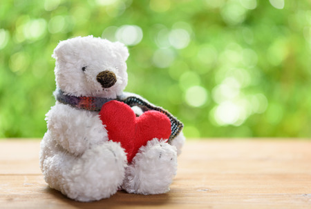 old desk: White puffy teddy bear toy hugging red heart sit alone on wood table with green blurred background Stock Photo