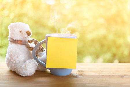 White puffy teddy bear and blue coffee cup,post it for text in morning sunlight on wood table top