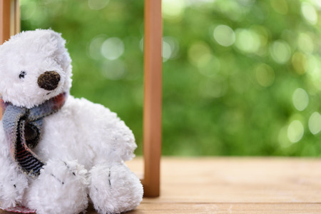 niños abandonados: White puffy teddy bear toy sit alone on wood table with green blurred background Foto de archivo