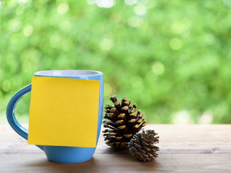 Blue coffee cup,post it for text and pine corn on wood table top with nature green blurred background