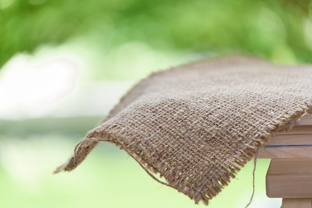 white fabric texture: Sackcloth on wood table top with nature green blurred backgroun,space for products