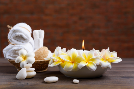 salon: Spa wellness and treatment with essential oils,zen stone,towels,candle,hearbal massage ball and frangipani flowers on wooden table with brick wall background Stock Photo