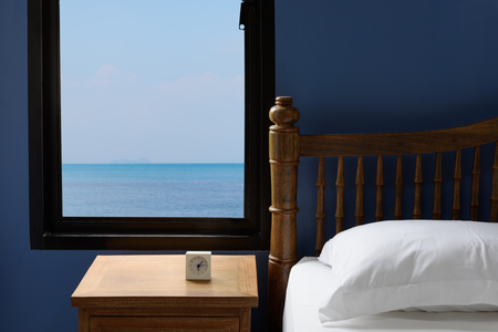 window view: Interior white pillows and bedding sheet in blue bedroom with summer sea view background in morning
