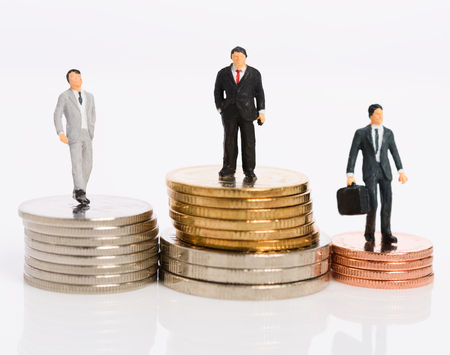 Miniature business people stand on money coins isolated on white,Business competition winner concept Stock Photo