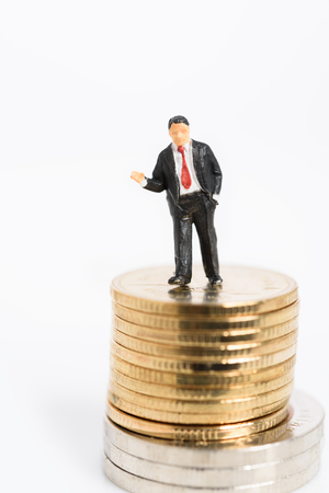 Miniture success businessman in black suit stand on golden and silver coins isolated on white background Stock Photo