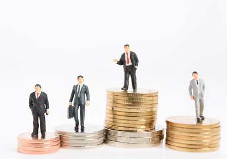 Miniature business people stand on money coins isolated on white,Business success and leadership concept Archivio Fotografico