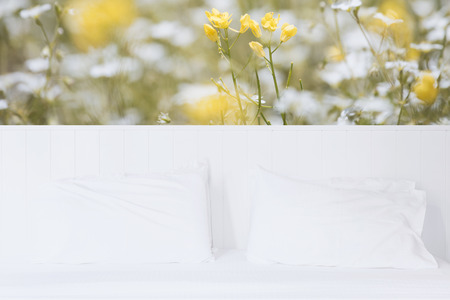 White pillow and bedding in modern white bedroom interior with beautiful yellow flowers wallpaper background Stock Photo