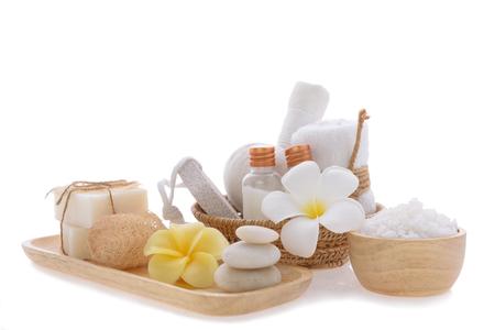 Het concept van kuuroordwellness, witte kaars, melkzeep, zout, handdoek, bloemen en kruidenmassagebal op houten dienblad isoleert met het knippen van weg