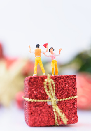 Miniature lover couple with red heart over Christmas ornaments background Standard-Bild