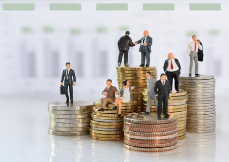 Concept d'entreprise réussie, équipe commerciale miniature sur des pièces d'or avec fond de graphique