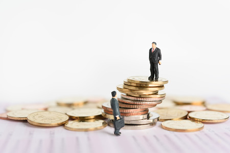 Miniature business people stand on pile of money coins with book bank background,Business competition winner concept Stock Photo