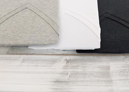 New black, white and grey v neck shirt on white wooden background