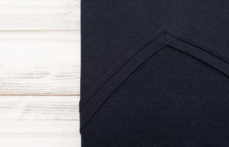 New black v neck shirt on white wooden background