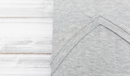 New gray v neck shirt on white wooden background