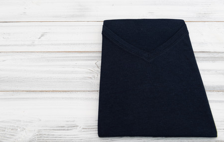New black v neck shirt on white wooden background
