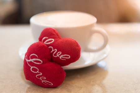 Hot coffee cup with red hearts shape symbol on marble table  in coffee shop background