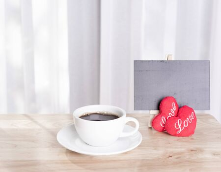 Hot coffee cup with red hearts shape symbol and black board on wood table with white curtain background