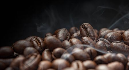 Aroma roasted coffee beans with smoke rising over dark background 스톡 콘텐츠