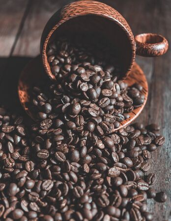 Roasted coffee beans in wood cup on wooden background