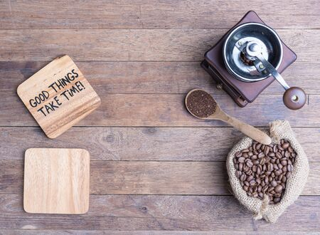 Coffee grinder,coffee beens in burlap and blank wood plate  on wooden table background,flat lay with copy space