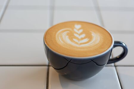 Latte art coffee cup on white table