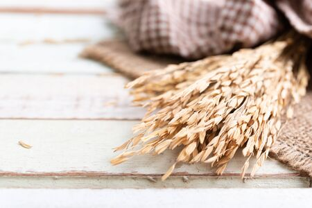 Bouquet dry ears of rice Thai jusmine and burlap or sackcloth on wood table.,top view