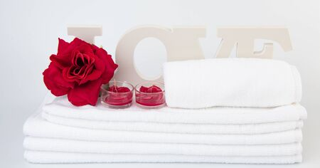 Spa wellness with red rose candles ,white towel and love text on white background Archivio Fotografico