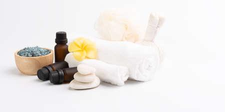 Spa massage, exotic tropical plumeria flowers ,serum,herb scrub,zen stones, white towels and blue salt crystal  on white background