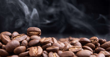 Aroma roasted coffee beans with smoke rising over dark background