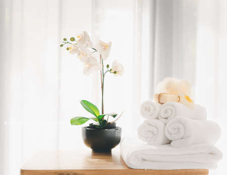 Spa products with white towels,soap,luffa scrub,comb and beautiful orchid flower in clean white room 版權商用圖片 - 157298844