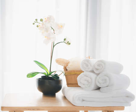Spa products with white towels,soap,luffa scrub,comb and beautiful orchid flower in clean white room