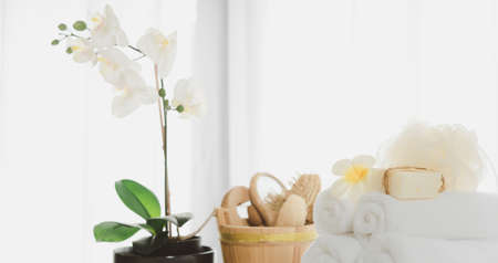 Spa products with white towels,soap,luffa scrub,comb and beautiful orchid flower in clean white room 版權商用圖片 - 157468597