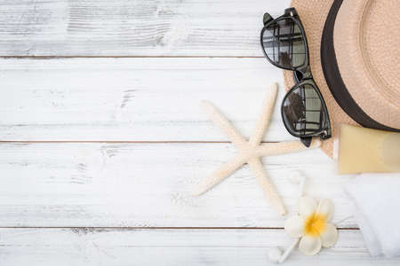Summer background,straw hat ,towel,ear phone and sunglasses with star fish on white wood table 版權商用圖片 - 157468635