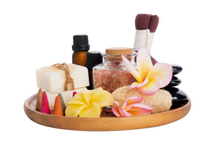 Spa products with  organic soap,luffa scrub,compress ball,pink salt,black stones, and beautiful plumerai flower on wooden tray isolated on white background with clipping path. 版權商用圖片