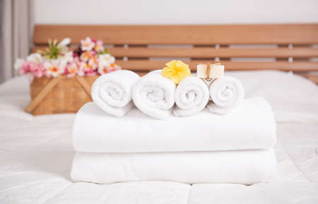 White towels,soap,candle and beautiful frangipani or plumeria flowers in bamboo wooden basket  on modern white bedroom 版權商用圖片